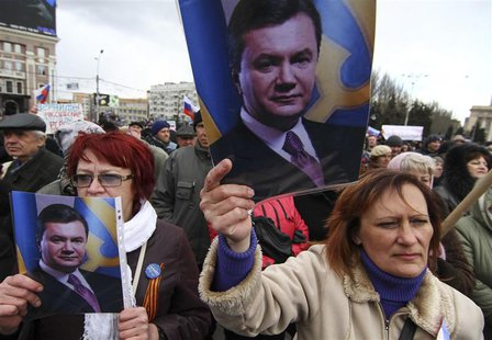Pro-Russian activists hold pictures of ousted Ukrainian President Victor Yanukovich during a protest in central Donetsk March 29, 2014. Russ