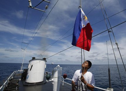 A Philippine Navy crew member aboard a civilian supply ship raises a Philippine national flag after the ship was able to evade an attempted