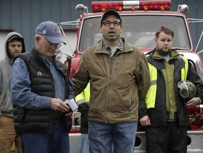 Darrington Mayor Dan Rankin (2nd R) and Pastor Mike De Luca (2nd L) lead workers and community members in prayer and a moment of silence mar