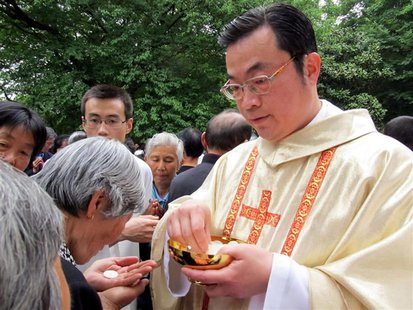 Rev. Thaddeus Ma Daqin gives the holy communion to a woman at Sheshan Cathedral, Shanghai in this April 30, 2012 picture provided to Reuters