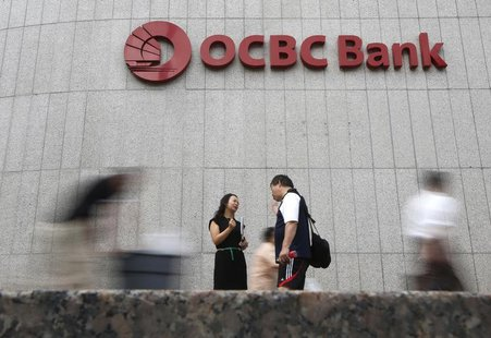 Office workers pass a logo of Overseas-Chinese Banking Corp Ltd (OCBC) at the company's headquarters in Singapore February 14, 2014. REUTERS