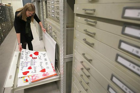 Archivist Marta Crilly looks through a file drawer of posters saved from the makeshift memorial that arose following the 2013 Boston Maratho