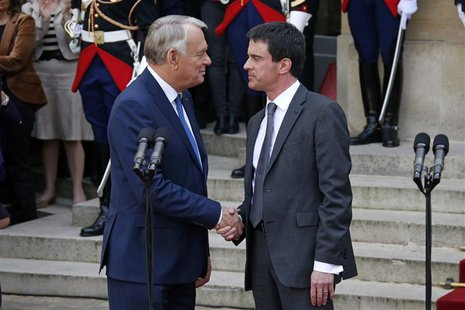 France's outgoing Prime Minister Jean-Marc Ayrault (L) shakes hands with newly-named Prime Minister Manuel Valls during the official handove