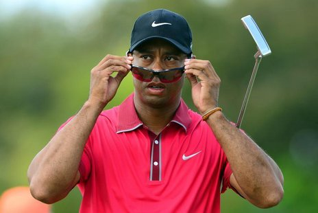 Mar 9, 2014; Miami, FL, USA; Tiger Woods puts on his sunglasses on the 3rd hole green during the final round of the WGC - Cadillac Champions