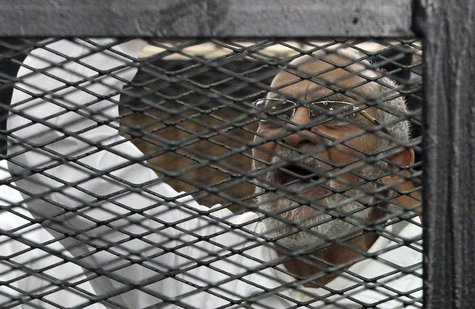 Muslim Brotherhood leader Mohammed Badie shouts slogans from the defendant's cage during his trial with other leaders of the Brotherhood in