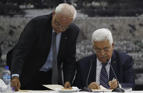 Palestinian chief negotiator Saeb Erekat (L) helps Palestinian President Mahmoud Abbas as he signs international conventions during a meetin