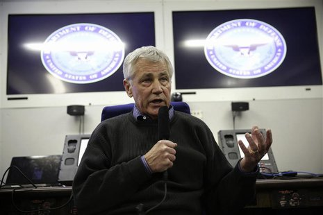 U.S. Secretary of Defense Chuck Hagel speaks to members of a travel press pool on a plane en route to Honolulu, Hawaii April 1, 2014. REUTER