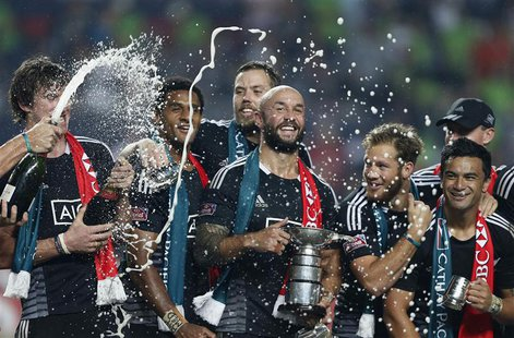 New Zealand captain D J Forbes holds the trophy as he celebrates with his teammates after beating England in the Cup final of the Hong Kong
