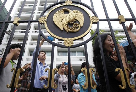 Thailand's Finance Ministry officers stand behind the ministry's gate while anti-government protesters rally outside in central Bangkok Apri