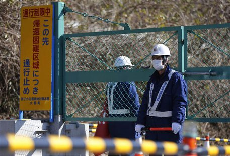 Security personnel stand guard near a steel gate that marks the border between Tamura and Okuma town in Okuma town, Fukushima prefecture Apr