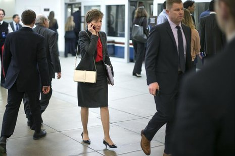 U.S. Senator Susan Collins (R-ME) (C) talks on a mobile phone as she arrives for the weekly Republican caucus luncheon at the U.S. Capitol i