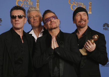 Adam Clayton, Bono, Larry Mullen, Jr., and The Edge (L to R), from the band U2, pose backstage with their award for Best Original Song for ""