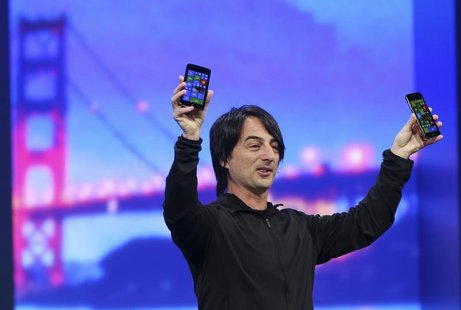 Joe Belfiore, vice president of the operating system group at Microsoft, holds a pair of mobile phones featuring the new Windows 8.1 operati