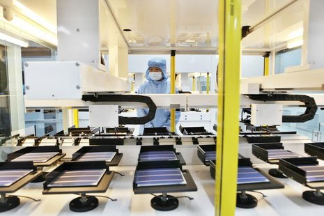 An employee works along a solar panel production line at a factory of Shanghai Chaori Solar Energy Science and Technology Co Ltd, in Jiujian