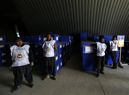 Afghan election commission stand by before preparing to send ballot boxes and election material to polling stations at a warehouse in Kabul
