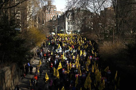 Members of the Service Employees International Union (SEIU) march out of Central Park onto 5th Avenue during a protest in support of a new c