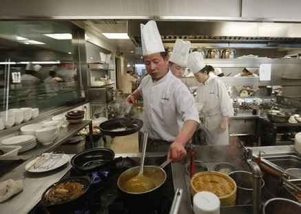Chiefs cook a meal at a restaurant inside a shopping mall in a wealthy district in Beijing February 25, 2013. REUTERS/Kim Kyung-Hoon