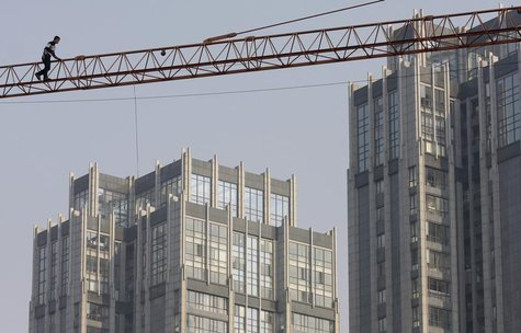 A labourer walks on a crane at a construction site in Nanjing, Jiangsu province December 14, 2011. REUTERS/Sean Yong