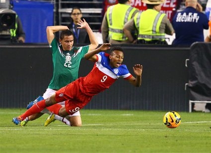 Apr 2, 2014; Glendale, AZ, USA; USA forward Julian Green (9) falls as he collides with Mexico defender Paul Aguilar (22) in the second half