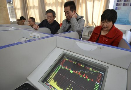 Investors look at computer screens showing stock information at a brokerage house in Fuyang, Anhui province March 21, 2014. REUTERS/China Da