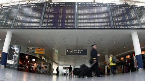 Pilots walk past a flight schedule board announcing cancelled flights of German airline Lufthansa at Munich's airport April 2, 2014. REUTERS