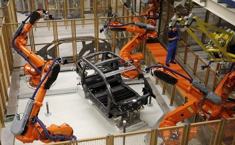 A worker makes technical measurements with robots on the carbon chassis at the serial production BMW i3 electric car in the BMW factory in L
