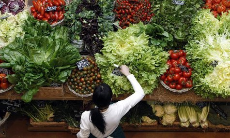 An employee arranges pricetags at a vegetables work bench during the opening day of upmarket Italian food hall chain Eataly's flagship store