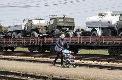 A woman walks with a pram along Ukrainian army vehicles on freight carriages ready to be sent from Crimea in the settlement of Gvardeiskoye