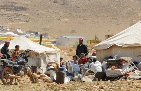 Refugees who fled the violence from the Syrian town of Flita, near Yabroud, stand outside their tents at the border town of Arsal, in the ea