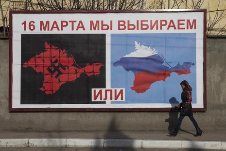 A woman walking by a poster calling people to vote in the upcoming referendum, in the Crimean port city of Sevastopol March 10, 2014. REUTER