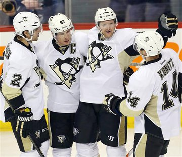 Apr 3, 2014; Winnipeg, Manitoba, CAN; Pittsburgh Penguins defenseman Paul Martin (7) celebrates with teammates after scoring a goal during t