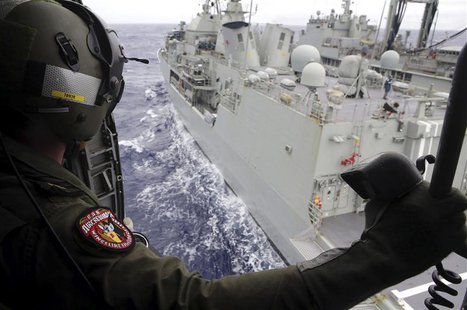 Leading Seaman Aircrewman Joel Young looks out from Tiger75, an S-70B-2 Seahawk helicopter, after it launched from the Australian Navy ship