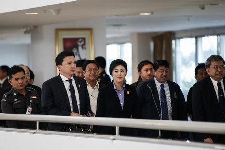 Thailand's Prime Minister Yingluck Shinawatra (C) leaves the Government Complex after a meeting with the Election Commission in Bangkok Dece