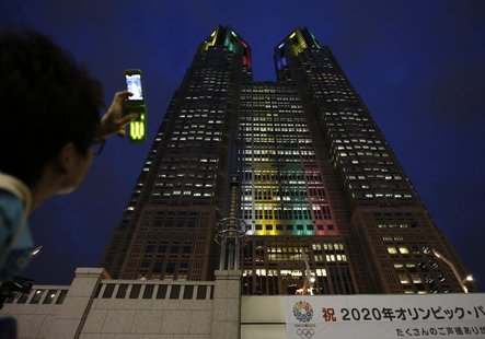 "A visitor takes photos of Tokyo Metropolitan Government Building illuminated in the Olympic colors before an event titled ""Tokyo 2020 Host C"