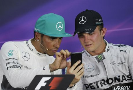 Race winner Mercedes Formula One driver Lewis Hamilton of Britain looks at the mobile device of team mate second-placed Nico Rosberg of Germ