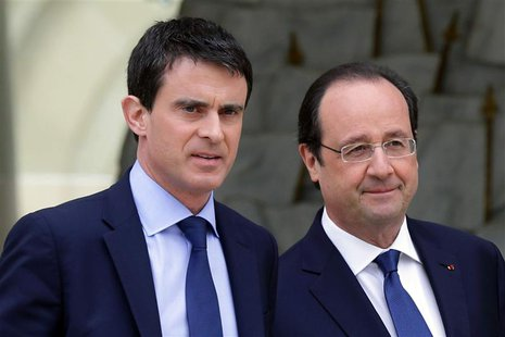 French President Francois Hollande (R) escorts newly-named Prime Minister Manuels Valls after the first cabinet meeting of the new governmen