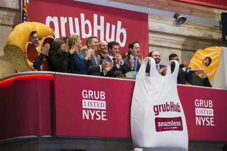 GrubHub CEO Matt Maloney (C) applauds after ringing the opening bell before the company's IPO on the floor of the New York Stock Exchange in