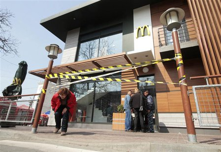 A woman makes her way under a barrier tape outside a McDonald's restaurant, which was earlier closed for clients, in the Crimean city of Sim
