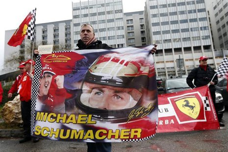 Philippe, a fan from Lyon, waves a flag as he attends a silent 45th birthday tribute to seven-times former Formula One world champion Michae