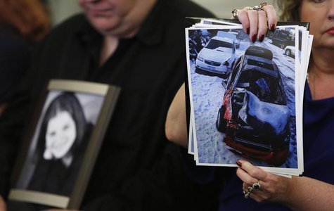 Surviving family member Leo Ruddy (L) holds a photo of his deceased daughter Kelly as his wife Mary Theresa holds up photos of Kelly's wreck