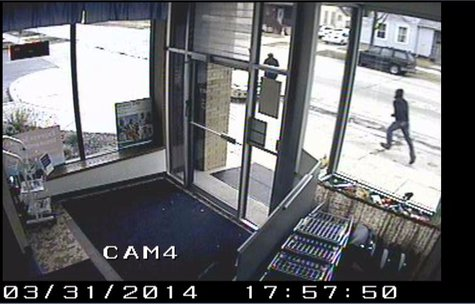 A surveillance picture of the Aurora Pharmacy purse snatching suspect prior to committing the crime March 31, 2014.