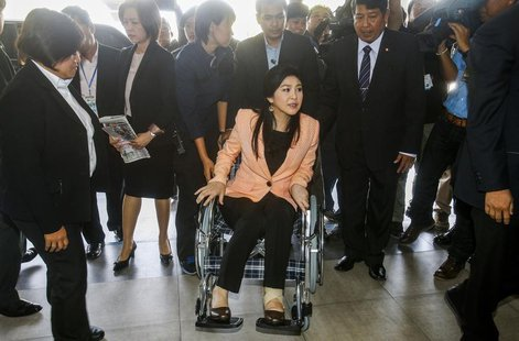 Thailand's Prime Minister Yingluck Shinawatra (C) arrives on a wheelchair at the Royal Police Cadet Academy in Nakorn Pathom province, March