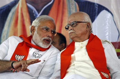 A leader of India's main opposition Bharatiya Janata Party (BJP), Lal Krishna Advani (R), listens to BJP prime ministerial candidate Narendr
