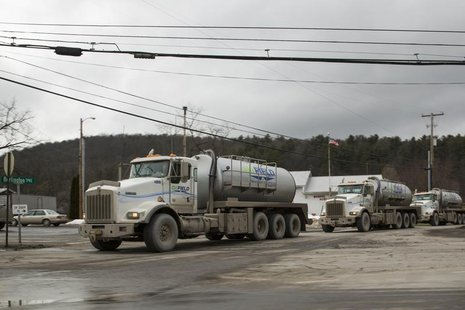 A line of trucks carrying water to Natural gas rigs make their way across the sprawling network of two lane roads between small towns to mak