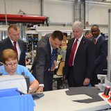 Gov. Rick Snyder watches as a seamstress sews leather pieces for high end automotive interiors at the Eissmann Group  Automotive plant. With the governor is Martin Wunsch, plant manager (left) and Dr. Klaus Elmer, CEO, Eissmann Group Automotive.