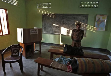 A policeman stands guard over an Electronic Voting Machine (EVM) at a polling booth ahead of the general elections in Majuli, a large river