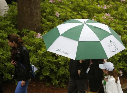 Patrons leave after play was suspended and the course closed due to inclement weather during a practice round ahead of the Masters golf tour