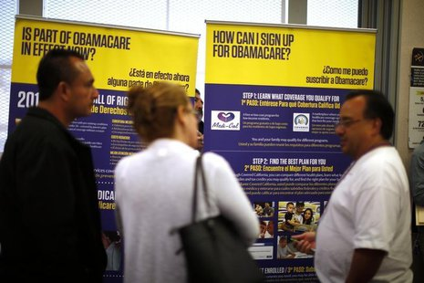 Julian Gomez (R) explains Obamacare to people at a health insurance enrolment event in Commerce, California March 31, 2014. REUTERS/Lucy Nic