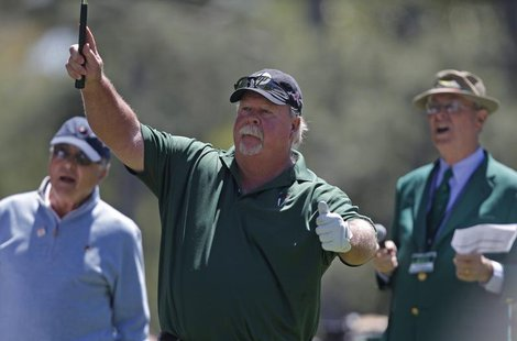 Craig Stadler (C) of the U.S. watches his hole-in-one on the first hole during the Par-3 tournament ahead of the 2011 Masters golf tournamen