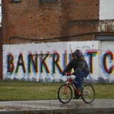 "A man rides his bike past graffiti that reads ""Bankruptcy"" in Detroit, Michigan, December 3, 2013. REUTERS/Joshua Lott"